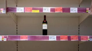Bottle of wine on an empty supermarket shelf