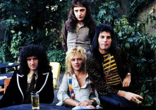 Brian May, John Deacon (standing), Roger Taylor and Freddie Mercury of British rock group Queen at Les Ambassadeurs where they were presented with silver, gold and platinum discs for sales in excess of one million of their hit single 'Bohemian Rhapsody', which was No 1 for 9 weeks on September 8, 1976 in London, England