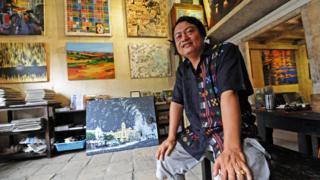 Gallery owner Aung Soe Min sitting in his gallery