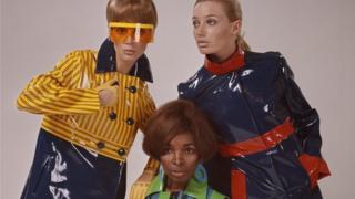 Renkli naylon yağmurluk giymiş üç kadın model