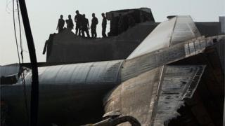 Military personnel and search and rescue teams comb through the wreckage of a military transport plane which crashed into a building on June 30, 2015 in Medan