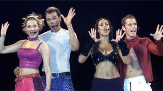 Four members of the Vengaboys, as they were in 2001, pose in the middle of the performance in front of the crowd.