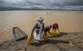 "Residents cross flooded land and canal in Madagascar""s capital Antananarivo, on Friday, March 10, 2017, to collect fresh water. Cyclone Enawo hit land Tuesday"