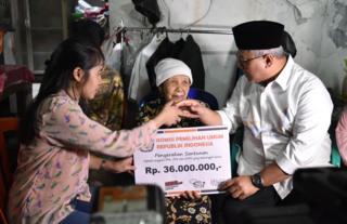 Ketua KPU Arief Budiman (kanan) menyerahkan santunan kepada keluarga almarhum Tutung Suryadi, petugas KPPS yang meninggal.