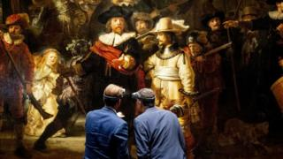General director Taco Dibbits (L) of the Rijksmuseum and Thierry Vanlancker (CEO) of AkzoNobel stand in front of Rembrandt van Rijn's The Night Watch in Amsterdam