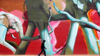 """A man walks past a huge graffiti artwork depicting elephants in downtown Johannesburg, South Africa, 10 October 2017. The artwork by """"Falko"""" is part of the newly formed graffiti tours that take people through the streets of the city to introduce them to the graffiti and who painted them."""