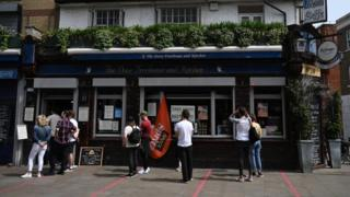 People observe social distancing outside a pub in east London