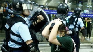 Policiais em confronto com manifestantes no aeroporto de Hong Kong