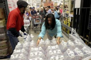 H-E-B employees remove bottles of water from a crate to hand out to customers Thursday morning, Dec. 15, 2016, in Corpus Christi, Texas.