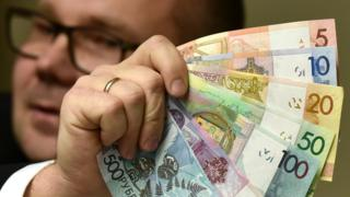 An official of Belarus' National Bank shows the new Belarus' ruble banknotes during a presentation in Minsk on November 10, 2015.