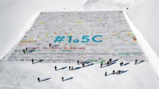 "The postcard, seen from above on the snow, reads: ""#1.5C - Stop global warming"". People walking underneath it look tiny by comparison, emphasising the scale."