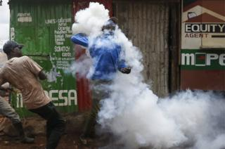 A supporter of the opposition coalition the National Super Alliance is covered by a cloud of tear gas as he throws a canister back at police officers