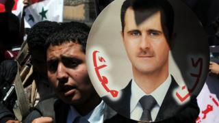 Esad posterleri taşıyan Suriyeliler
