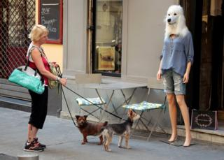 A woman looks at a store mannequin wearing a dog's head mask outside a fashion shop in Nice, France