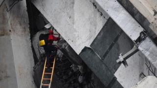 A rescuer climbs a ladder up into large slab of road concrete