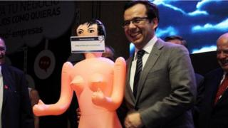 Chile's economy minister Luis Cespedes holds up an inflatable doll during an event of the exporters' association Asexma in Santiago, Chile, December 13, 2016.