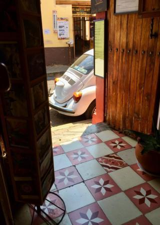 Volkswagen Beetle seen through a doorway from inside a building