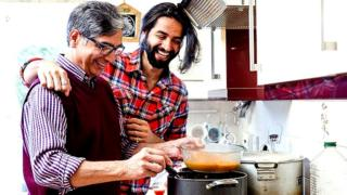 Mid adult man is looking over his father's shoulder as he prepares a curry at home
