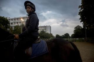 A young boy rides a horse