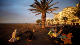 in_pictures A group of homeless men take in the last of the days light before seeking a place to sleep in South Africa