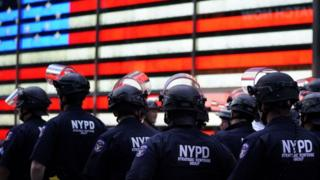 In this file photo taken on June 01, 2020 NYPD police officers watch demonstrators in Times Square on June 1, 2020, during a