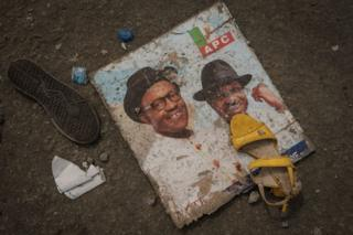 This picture taken on 13 February 2019, shows discarded shoes and a picture of Nigeria's President Muhammadu Buhari lying the ground in front of the main entrance of the Adokiye Amiesimaka Stadium, where 15 people were killed on 12 February 2019 in a stampede during a government election campaign rally in Port Harcourt, southern Nigeria.