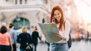 A girl reading a map in a European city