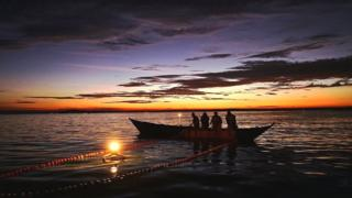 Fishermen on Lake Victoria as evening dalls