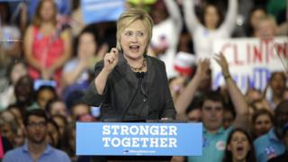 "Hillary Clinton at a rally, over a podium labelled ""stronger together"""