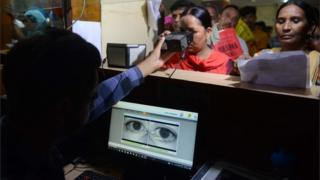 This photo taken on July 17, 2018 shows an Indian woman looking through an optical biometric reader that which scans an individual's iris patterns, during registration for Aadhaar cards (or unique identifier [UID] cards) in Amritsar