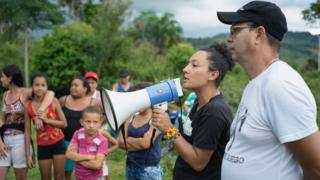 Isabel Zuleta addresses people with a megaphone