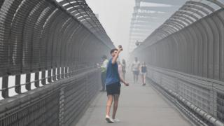 A man takes a photo as he crosses the Sydney Harbour Bridge amid heavy smoke