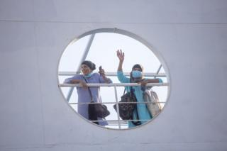 in_pictures Two masked women wave from the deck of a boat.