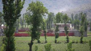 "Surrounded in red fabric, a compound is seen where locals reported a firefight took place overnight in Abbotabad, located in Pakistan""s Khyber Pakhtunkhwa province on May 2, 2011."