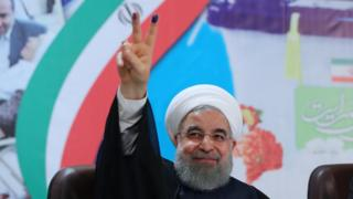 Hassan Rouhani holding up fingers covered in ink