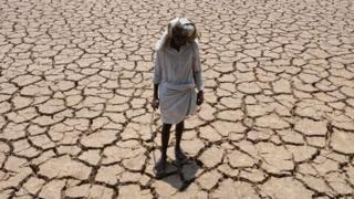 رجل هندي في أرضه الزراعية التي تعاني الجفاف