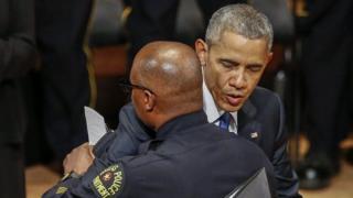 President Obama hugging police officer