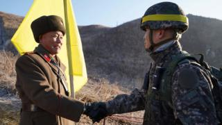 North and South Korean soldiers shaking hands