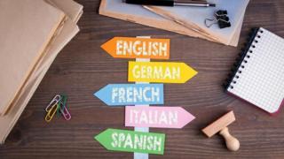 Carteles con nombres de idiomas sobre un escritorio