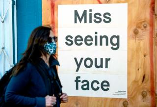 A woman in a face mask walks past a sign