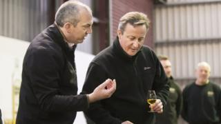David Cameron speaks to the master distiller at Old Bushmills whiskey distillery