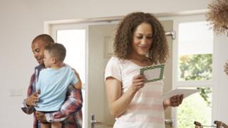 woman checks post in family hallway