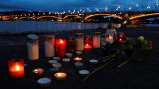 Candles burn at the river's bank near the site of a ship accident,