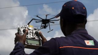 An employee of the Ivorian Electricity company (CIE) pilots a drone that ensures the monitoring of the hight voltage electric network, on July 10, 2017 in Bingerville, near Abidjan.
