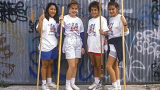 Four girls with brooms and rakes