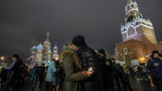 A young couple shares tender moments celebrating New Year on the Red Square in Moscow, Russia