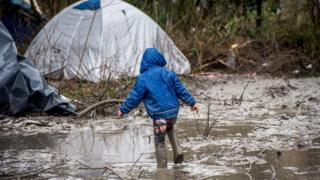 A refugee child walks in the mud in refugee camp in the coastal town of Grande-Synthe near Dunkirk, northern France, 10 January 2016