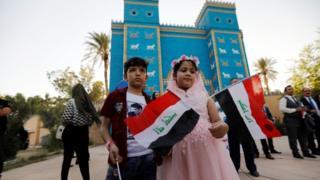Watoto walioshikilia bendera ya Iraq wakati wa sherehe baada ya Unesco kuutambua mji wa Babylon kama la kistoria duniani