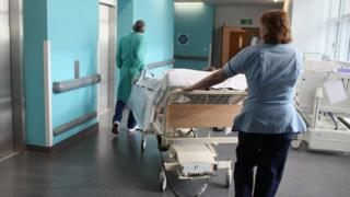Staff pushing a bed through a hospital