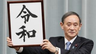 """El secretario en jefe del Gabinete de Japón, Yoshihide Suga, revela el nombre dela nueva era """"Reiwa"""" en una rueda de prensa en Tokio, 1 abril de 2019"""